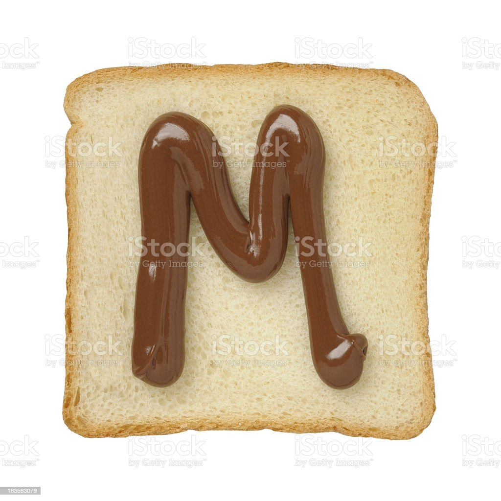 Chocolate letter M on a tinloaf slice, white background royalty-free stock photo