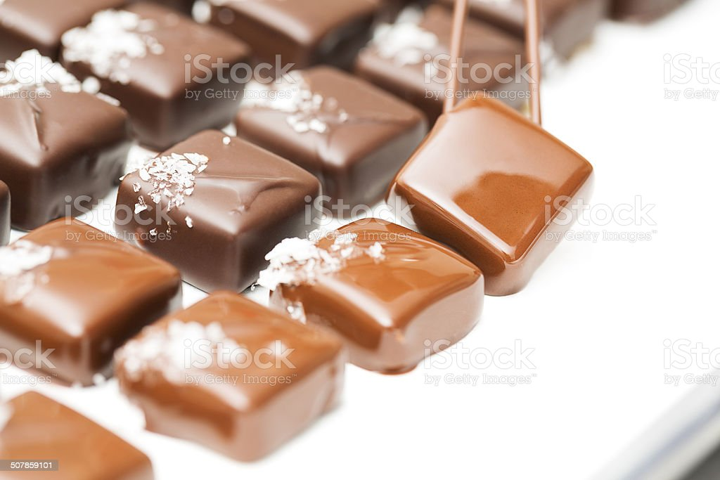 Chocolate making: rows of sea salt caramel truffles stock photo