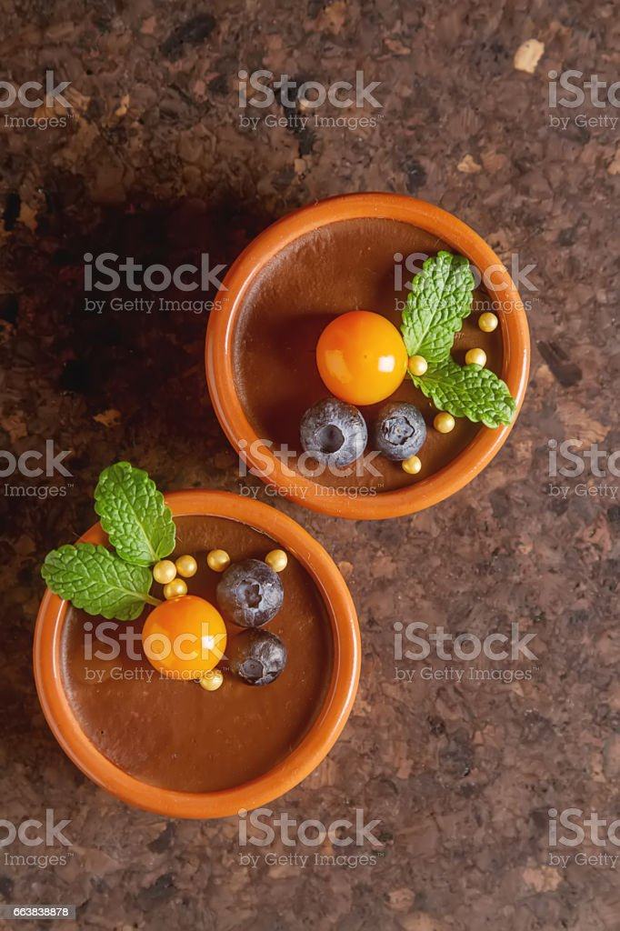 Chocolate mousse with berries in a ceramic bowl. Grey dark background. stock photo