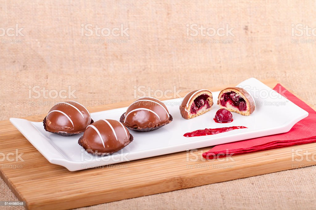 Chocolate muffin doughs with nuts and cherry on wood background stock photo