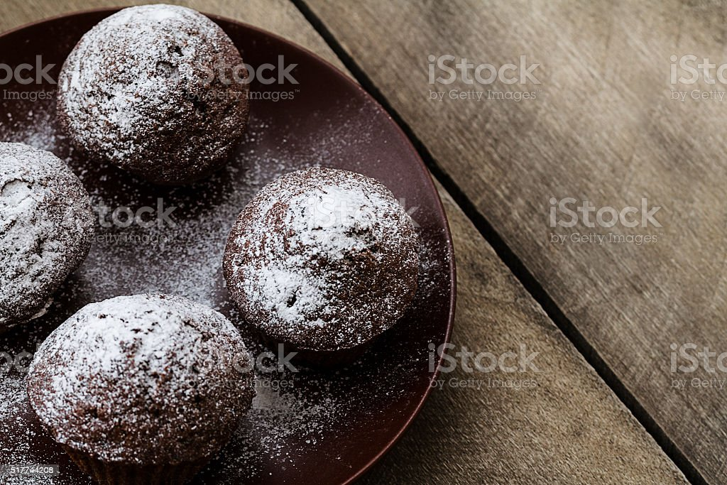 Chocolate muffins icing sugar on a wooden table stock photo