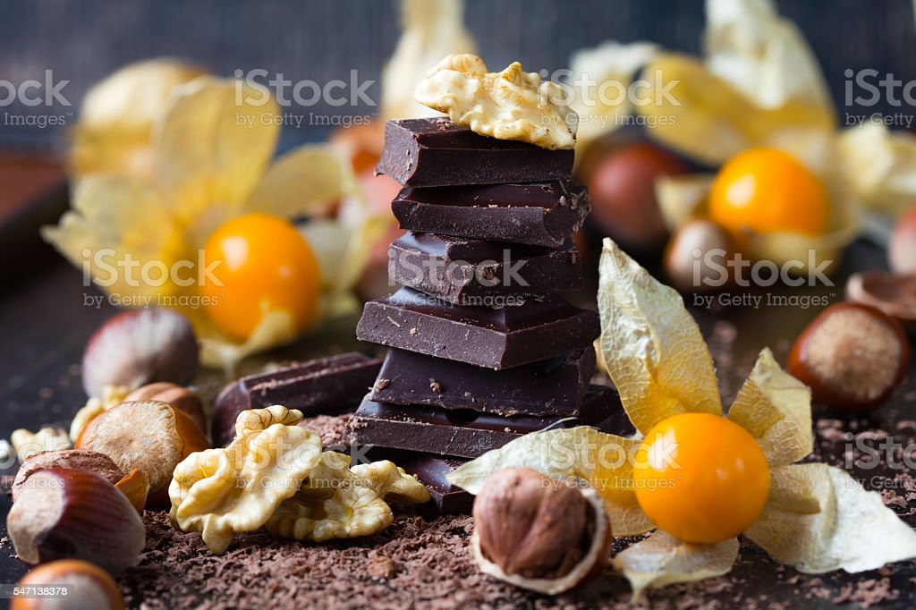 Chocolate, nuts, golden berries physalis on black background stock photo