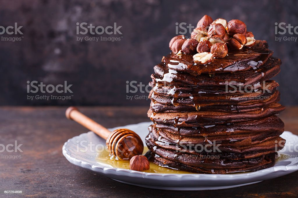 Chocolate pancake with honey and hazelnuts stock photo