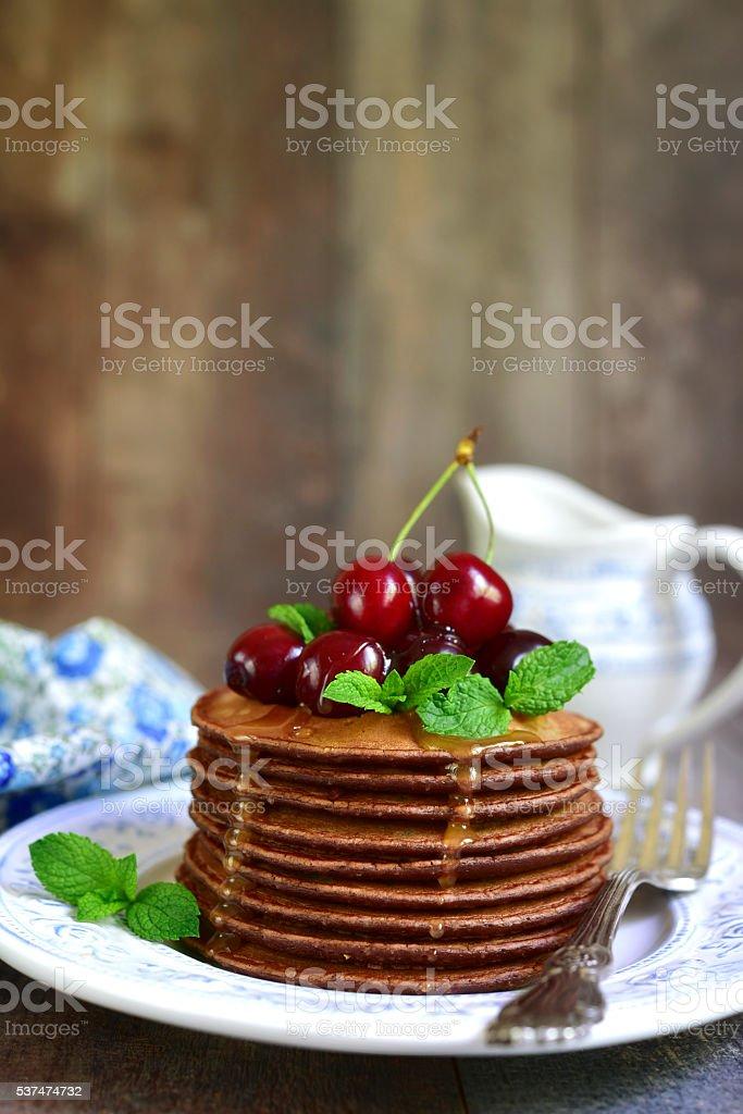 Chocolate pancakes with honey and cherry. stock photo