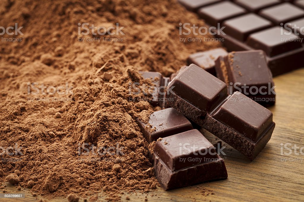 Chocolate pieces and ground cocoa on wood table stock photo