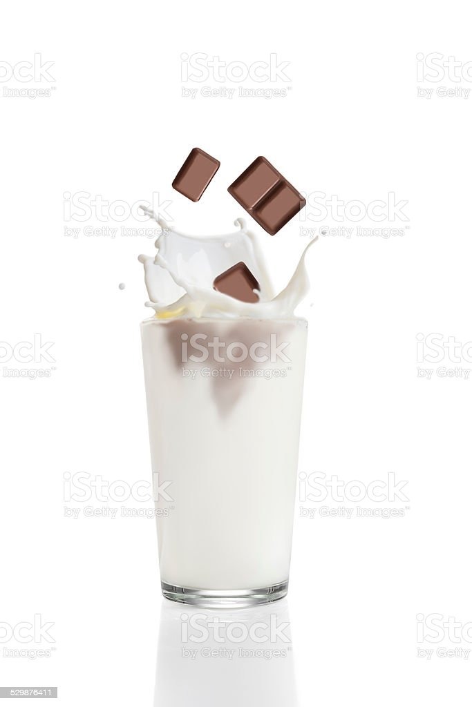 Chocolate pieces falling into glass with milk stock photo