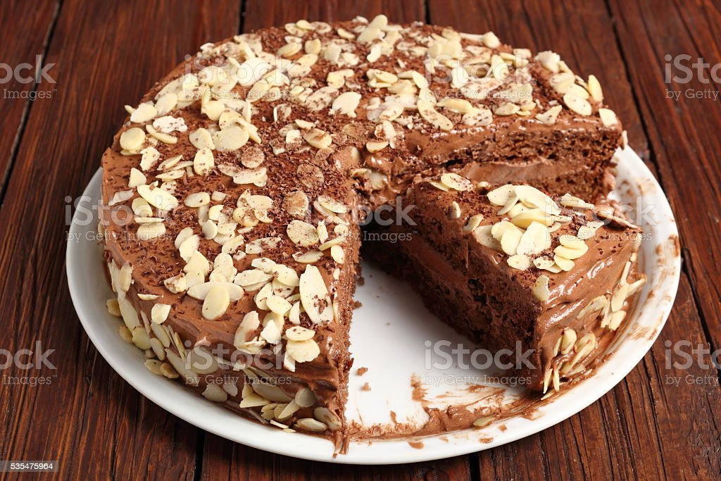 Chocolate sandwich cake garnished with flaked almonds stock photo
