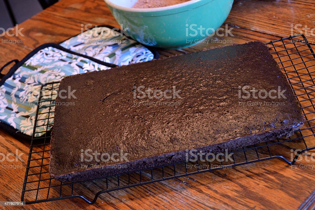 Chocolate sheet cake cooling on rack on wooden table stock photo