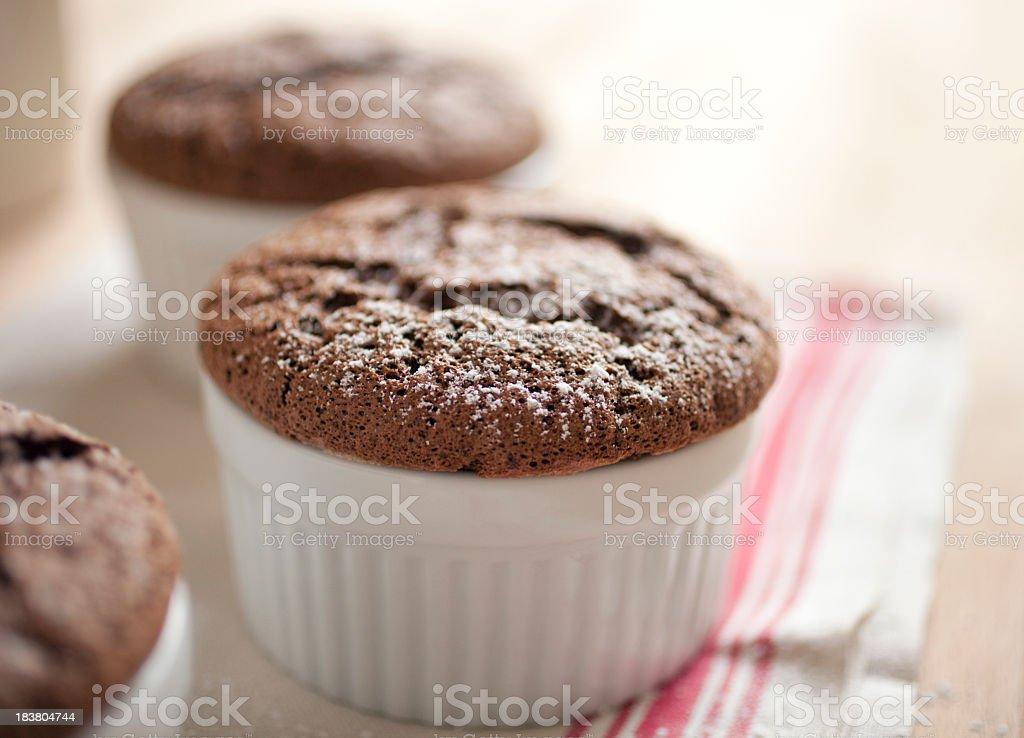 Chocolate souffles in white ramekin dishes stock photo