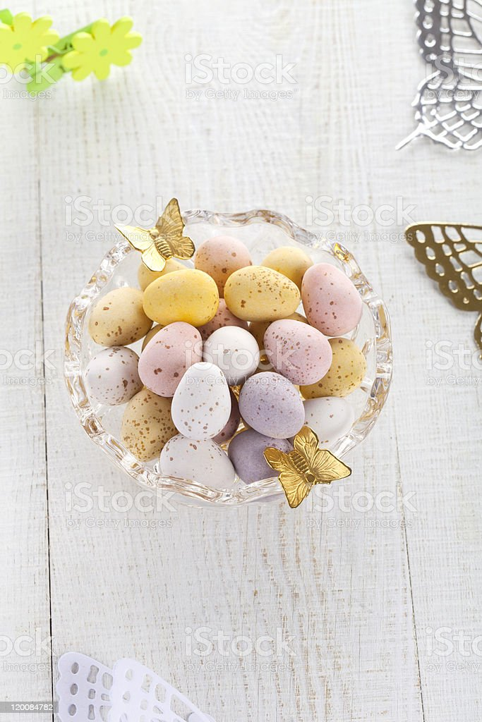 chocolate speckled eggs in bowl with batterfly on white table royalty-free stock photo