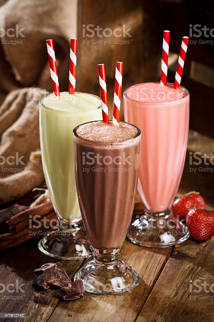 Chocolate, strawberry and vanilla milshakes in rustic wood table stock photo