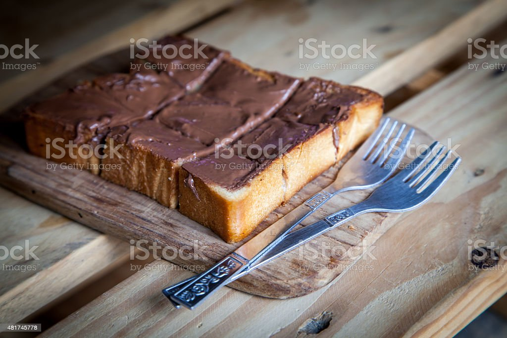 Chocolate sweet toast with fork on wooden table stock photo