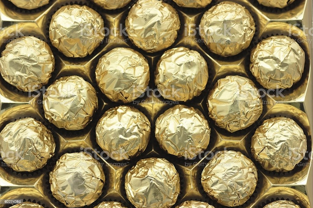 Chocolate sweets in golden foil royalty-free stock photo