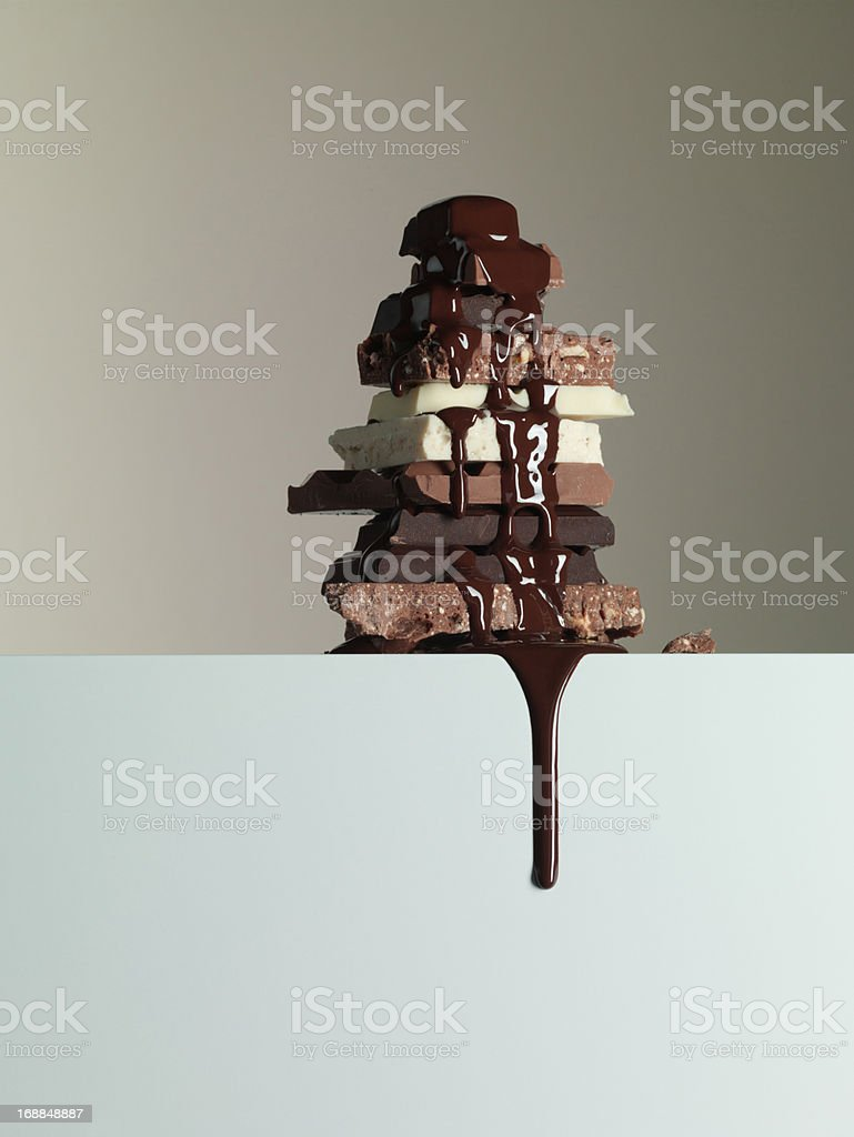 Chocolate syrup dripping over stack of chocolate bars royalty-free stock photo