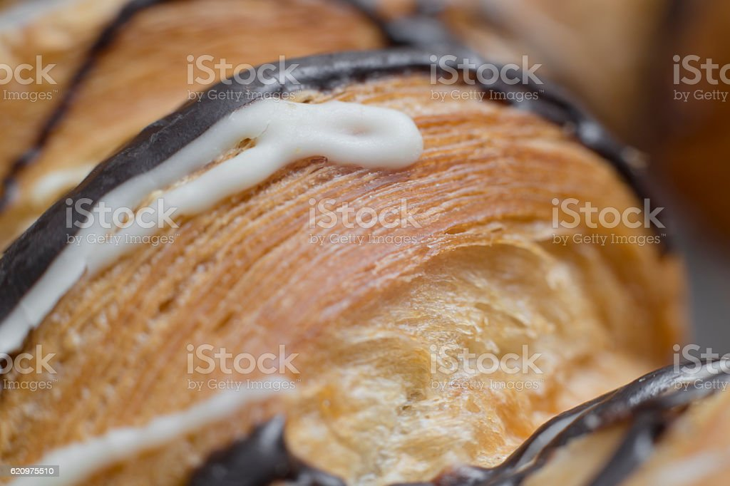 Chocolate syrup on baked croissant. Close up photo. stock photo