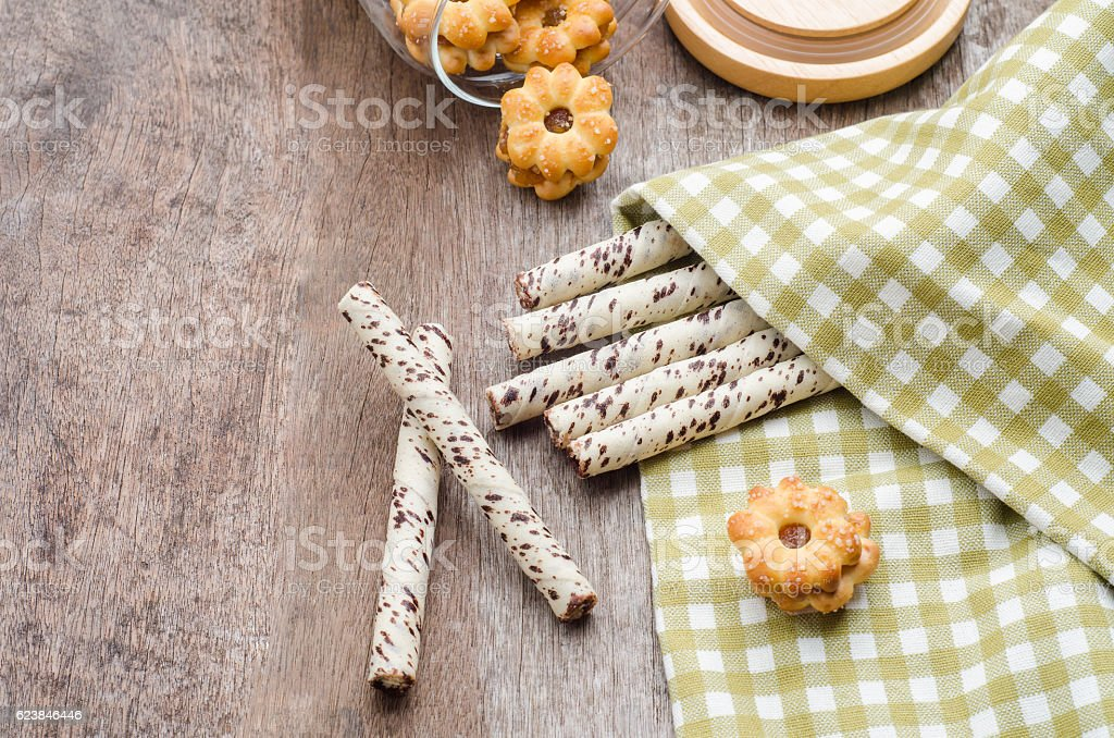 Chocolate wafer sticks and cookies on wooden table. stock photo