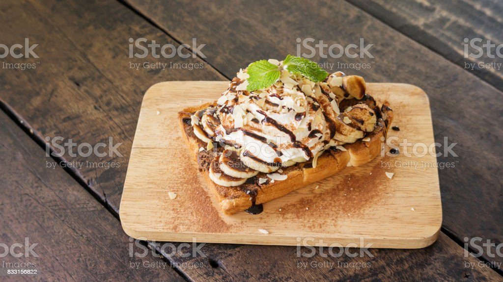 chocolate, whip cream, and banana on a bread. stock photo
