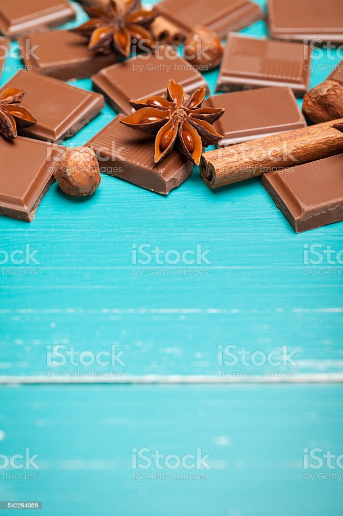 Chocolate with anise, cinnamon and hazelnuts on turquoise table stock photo