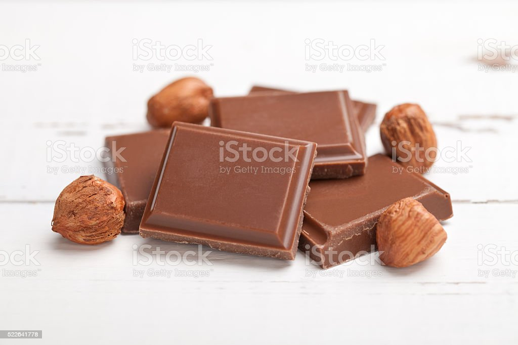 Chocolate with hazelnuts on white wooden table stock photo