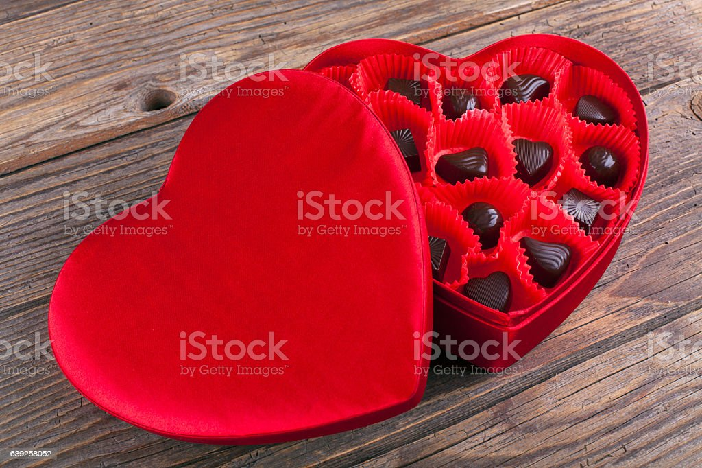 Chocolates in red heart box on wooden table stock photo