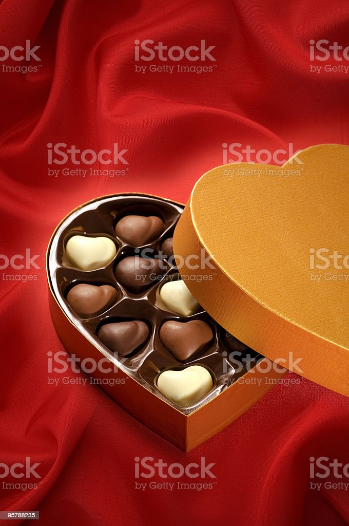 Chocolates on red satin background royalty-free stock photo