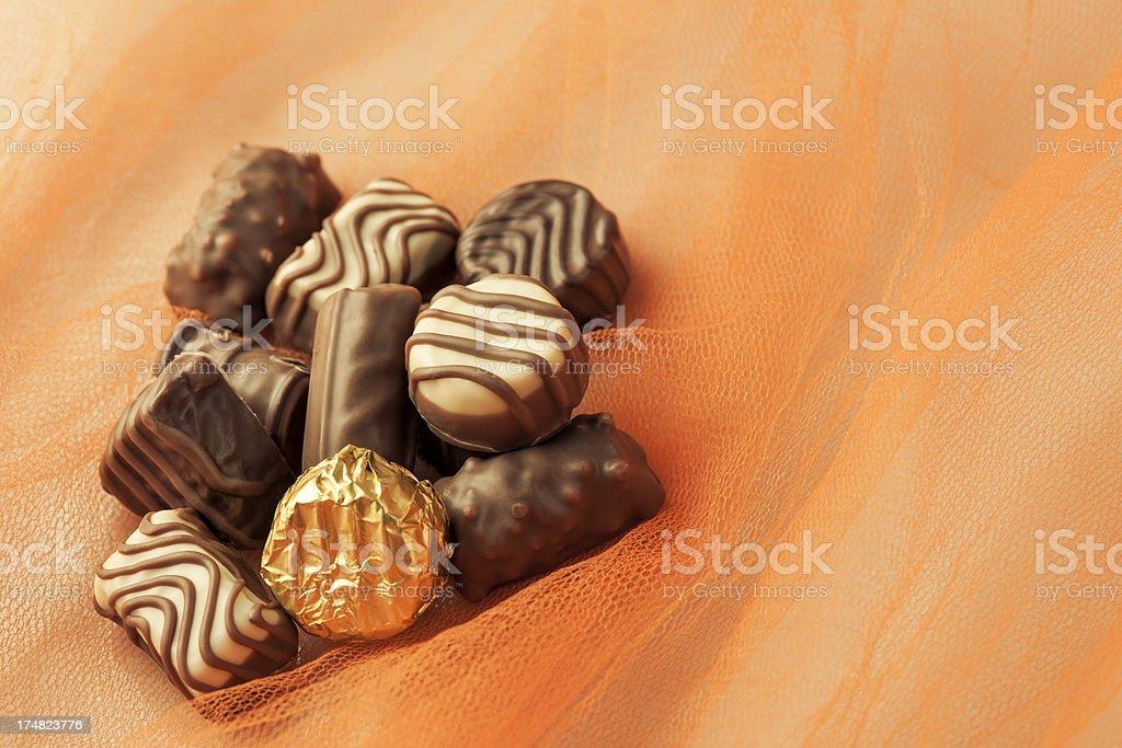 Chocolates on the orange background royalty-free stock photo