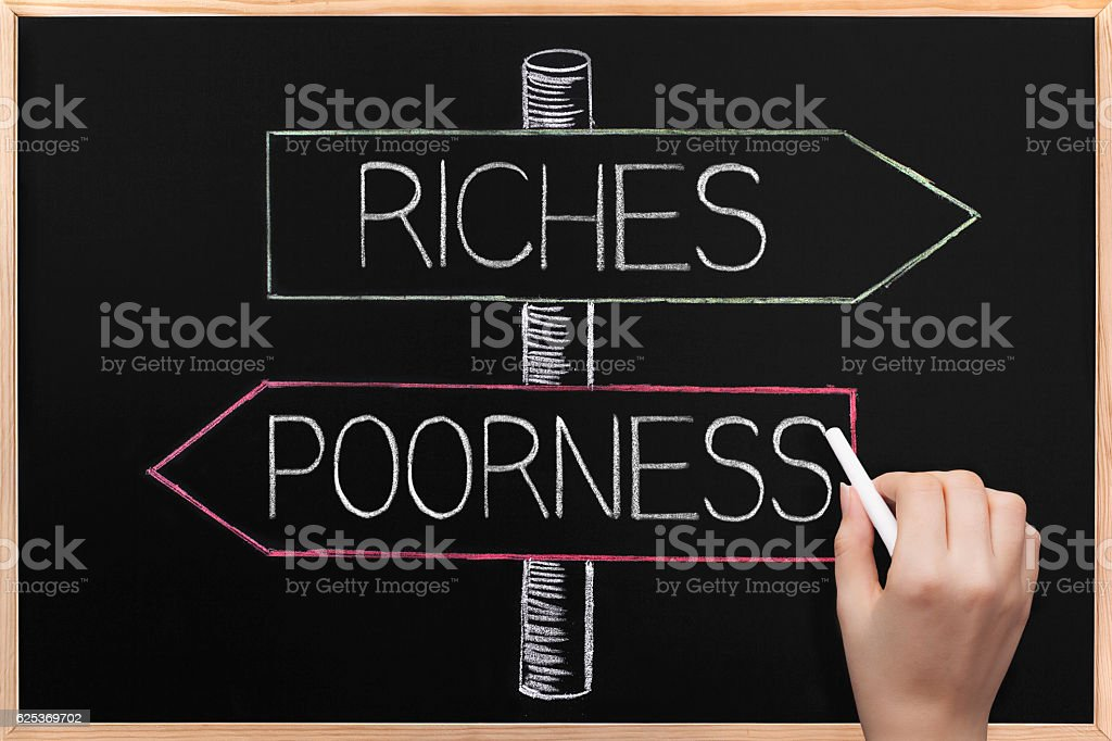 Choicе Riches or Poorness wrriten on opposite arrows on Blackboard stock photo