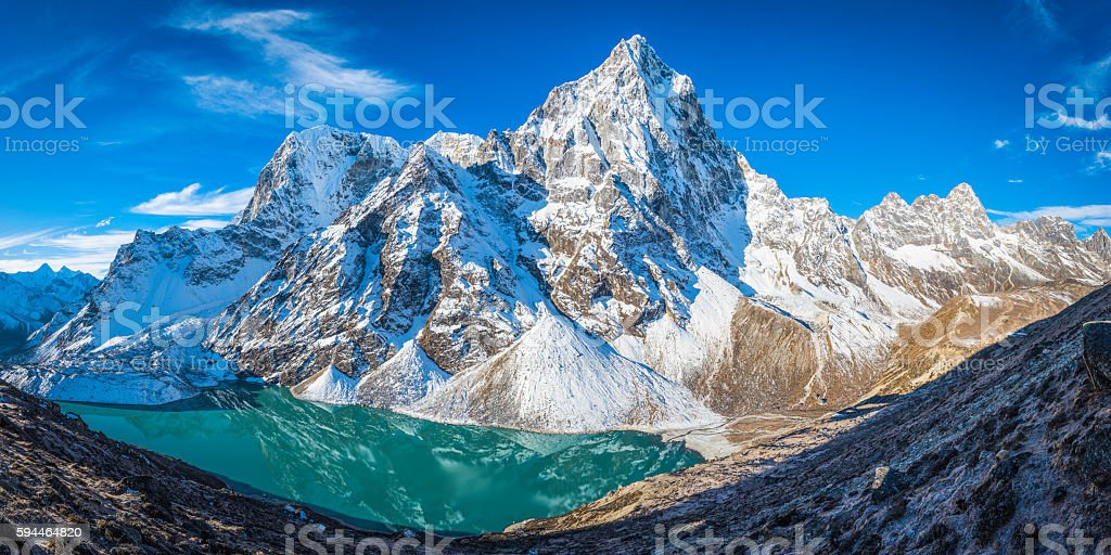Cholatse dramatic mountain peak towering over glacial lake Khumbu Himalayas stock photo
