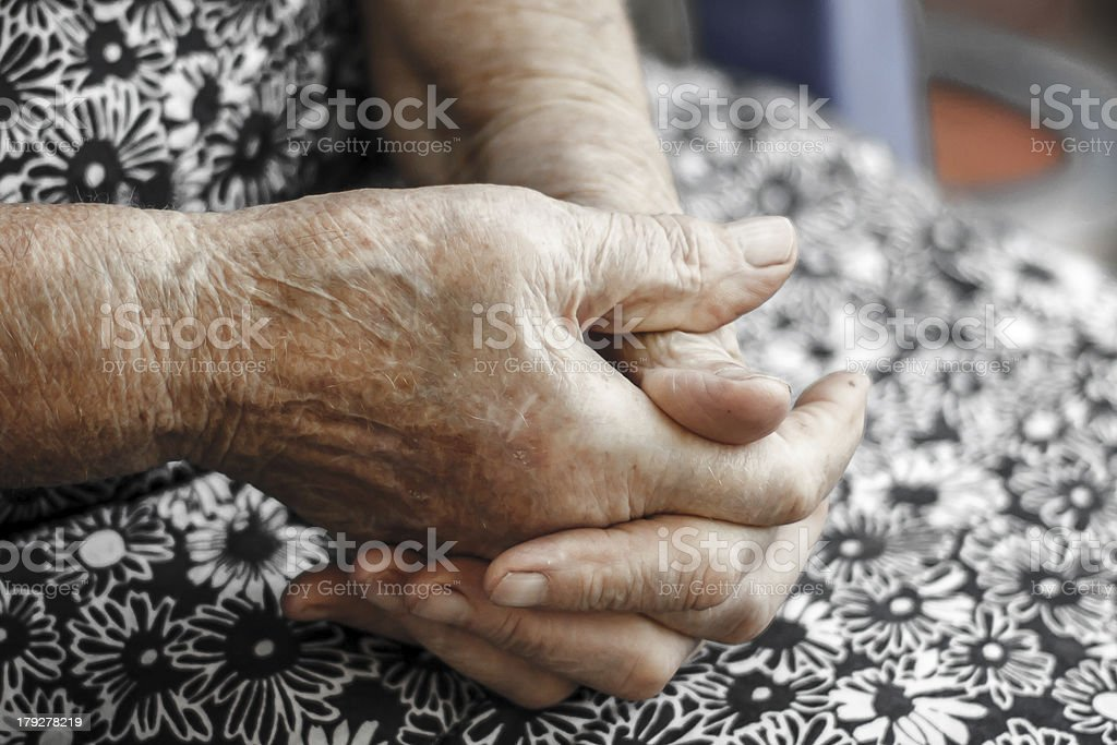Choose up of old woman clasping hands together in lap royalty-free stock photo