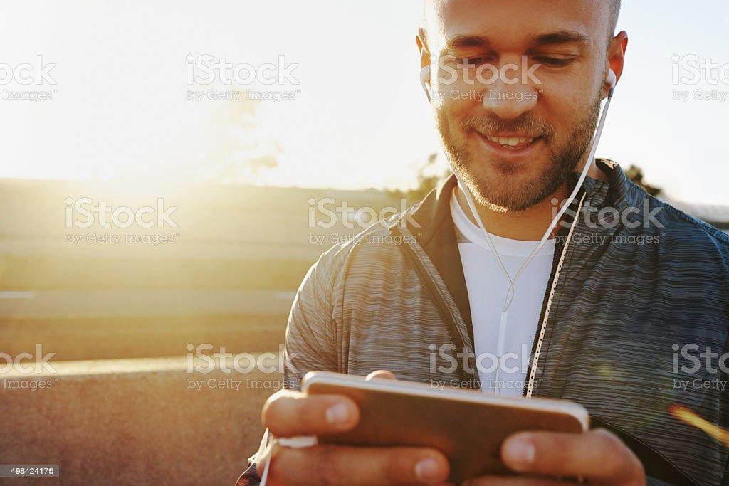 Choosing music that will motivate him on the run stock photo