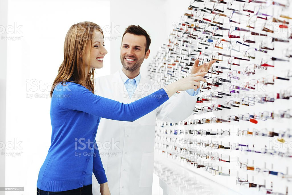 Choosing new glasses with help from the staff  stock photo
