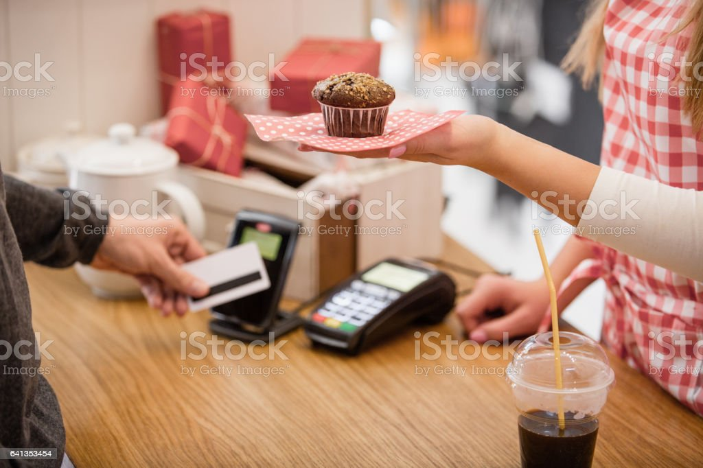 Choosing to pay muffin with contactless credit card reader stock photo