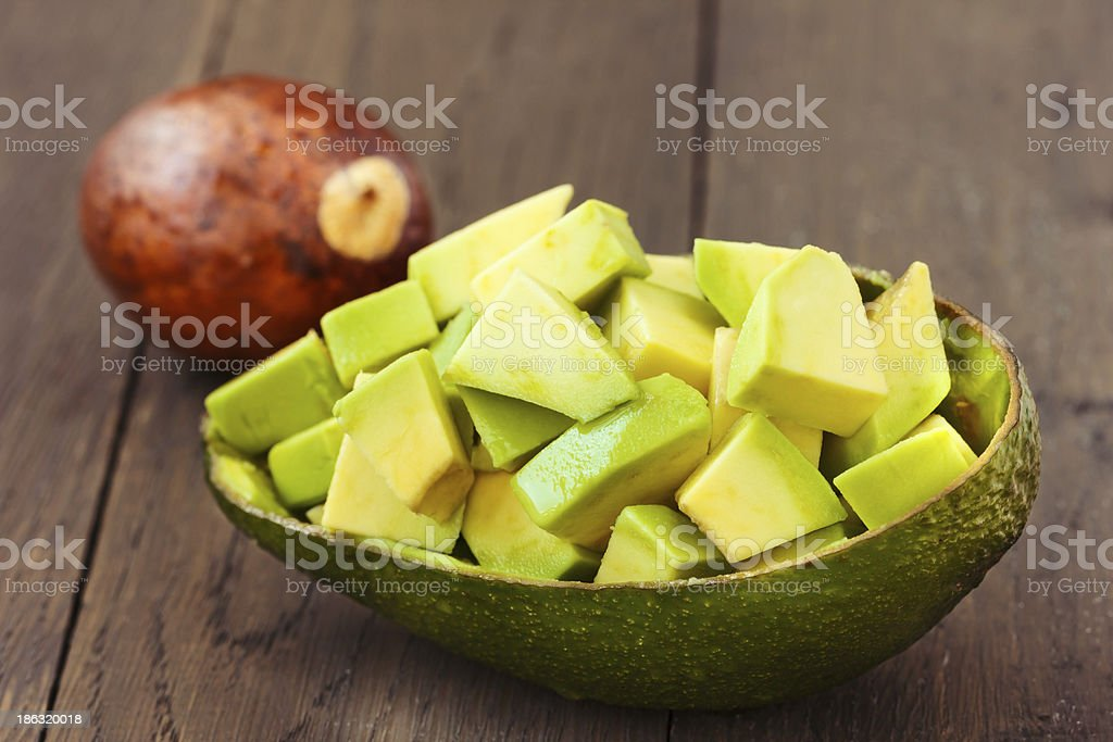Chopped avocado fruit on brown wooden old table stock photo