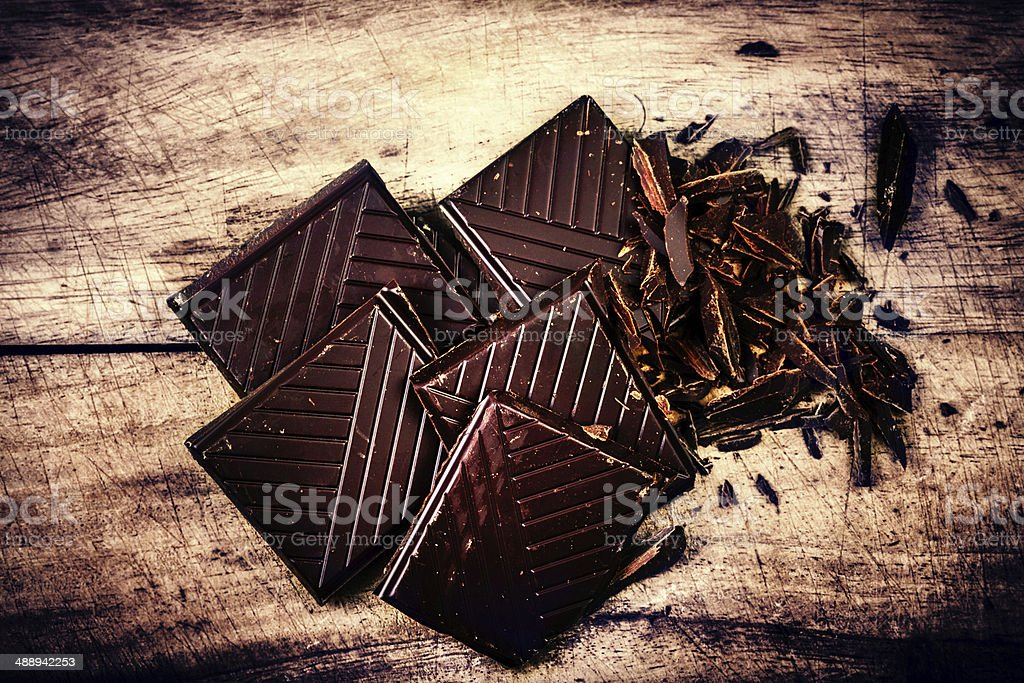 Chopped Chocolate Bar on wooden background closeup. Broken dark stock photo
