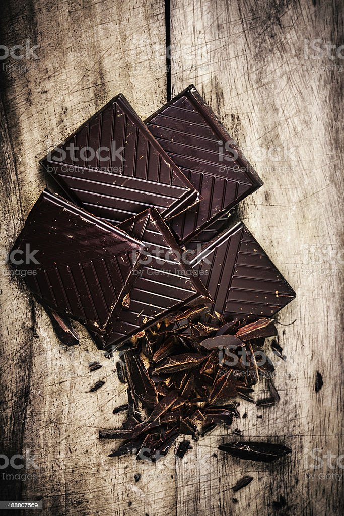 Chopped Chocolate Bar on wooden background closeup. Broken stock photo