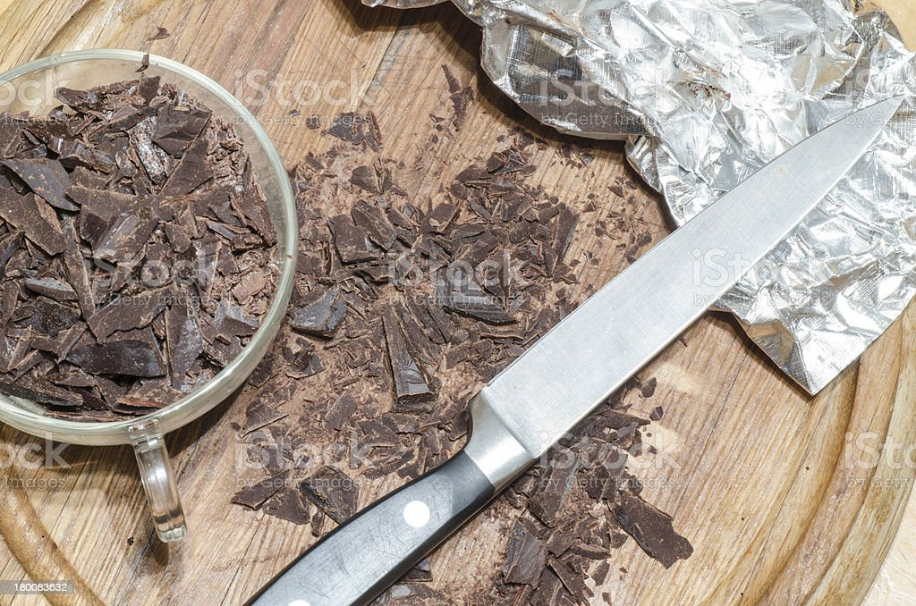 Chopped chocolate pieces on a wooden cutting board royalty-free stock photo