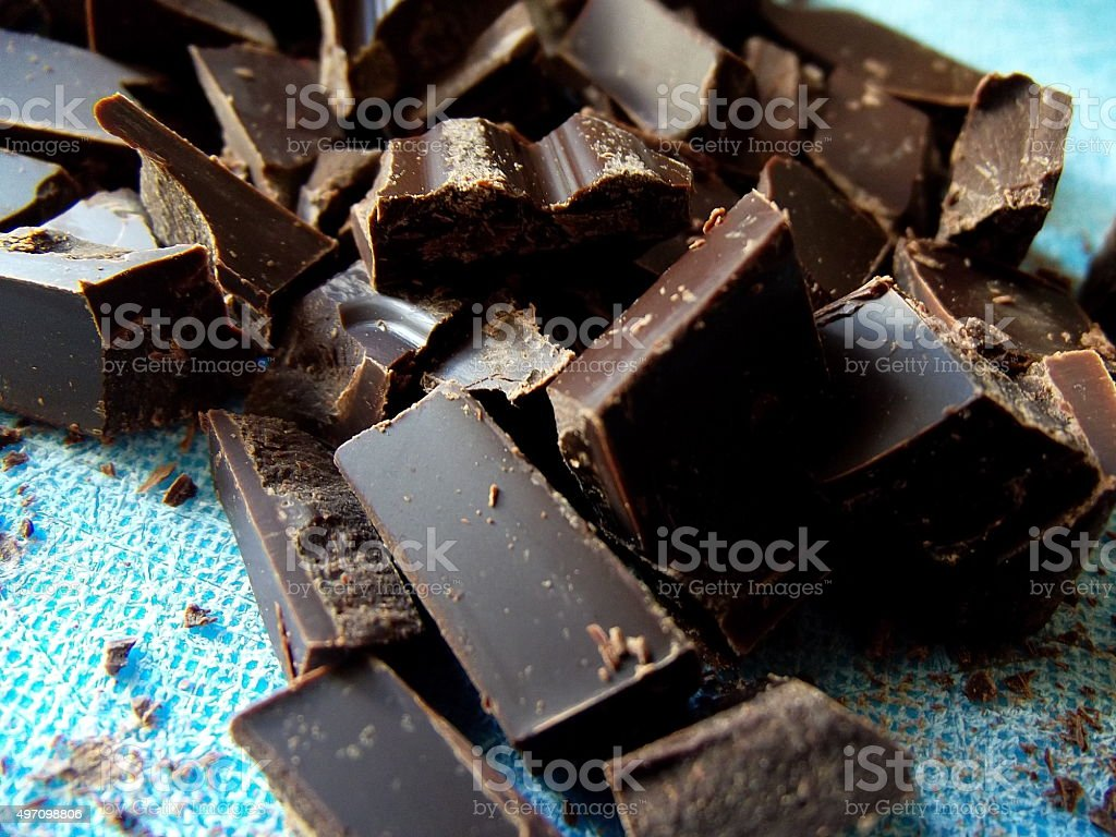 Chopped Dark Chocolate on Blue Cutting Board stock photo