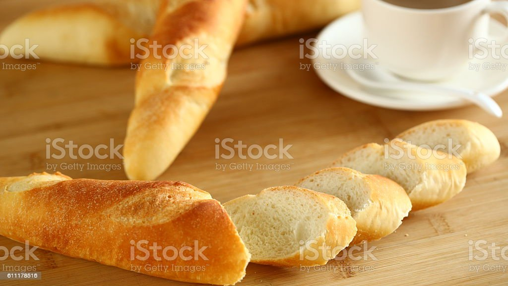 Chopped long bread on wooden cutting board stock photo