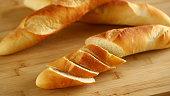 Chopped long bread on wooden cutting board