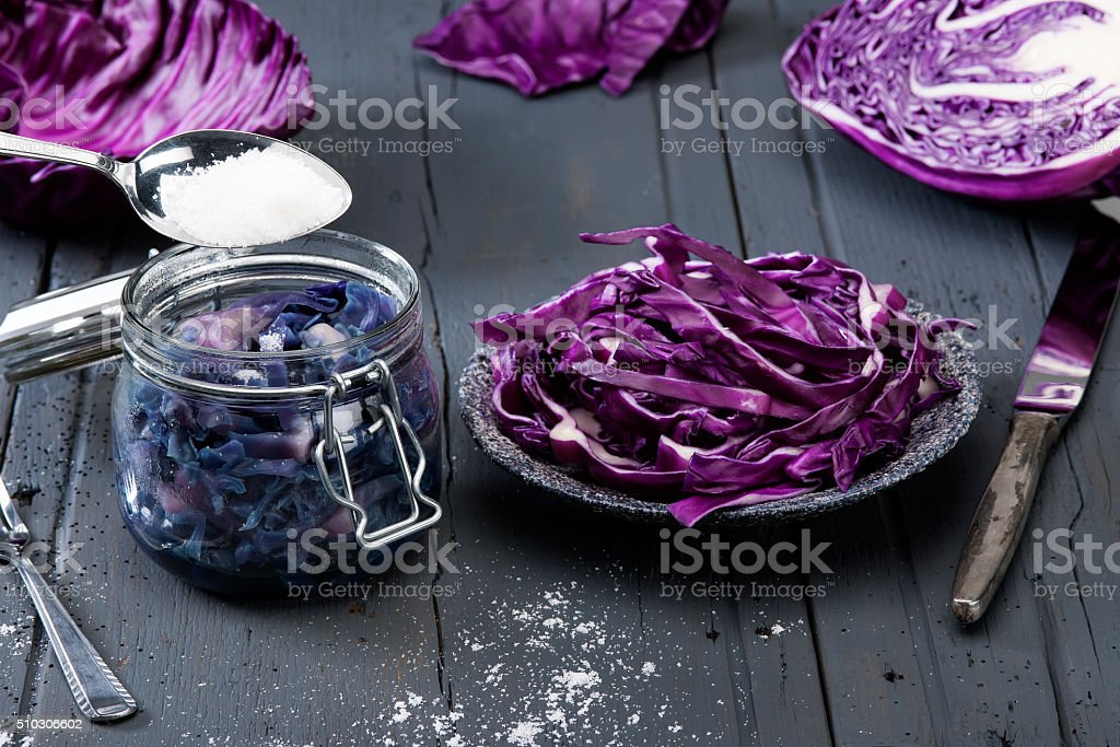 chopped red cabbage on old wooden table with preserving jar stock photo