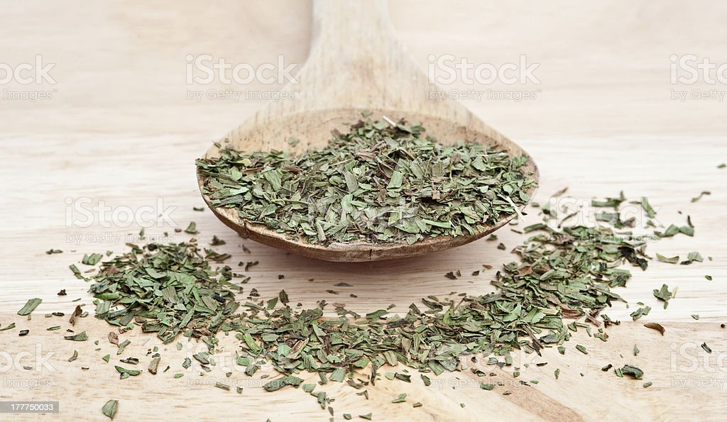 Chopped tarragon on wooden serving spoon with selective focus royalty-free stock photo