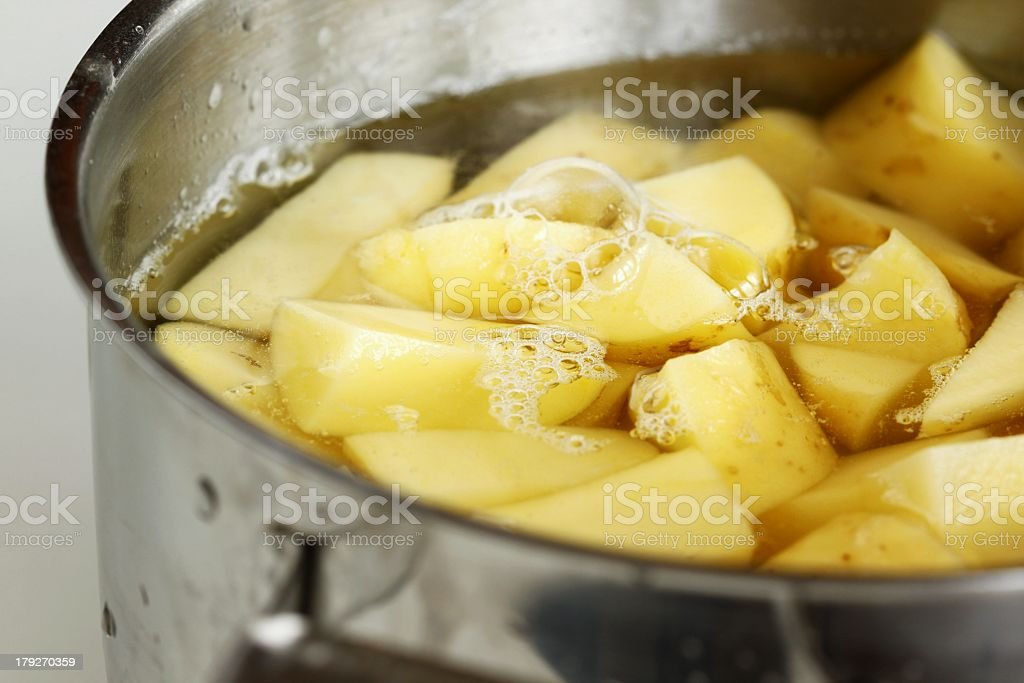 Chopped yellow potatoes in water in metal pot royalty-free stock photo