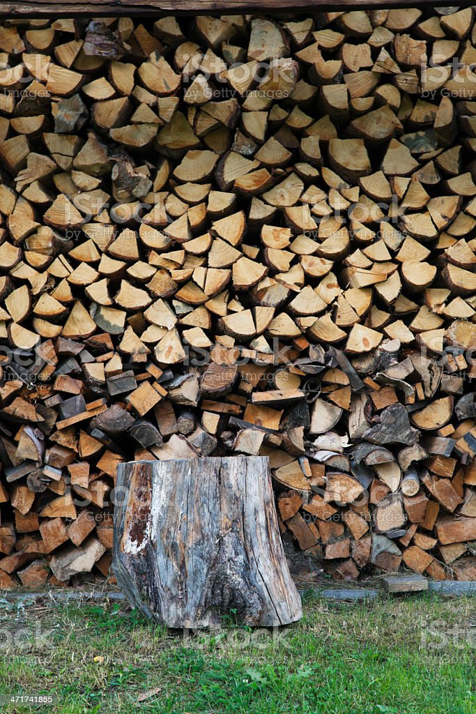 Chopping block and stacked logs royalty-free stock photo