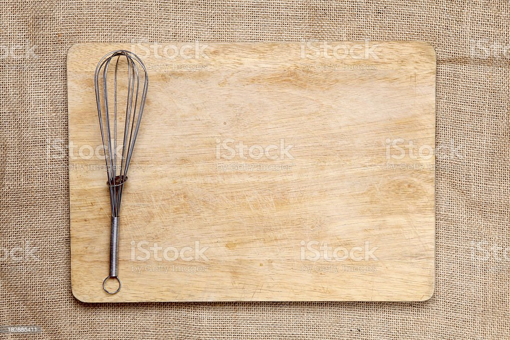 Chopping board and whisk stock photo