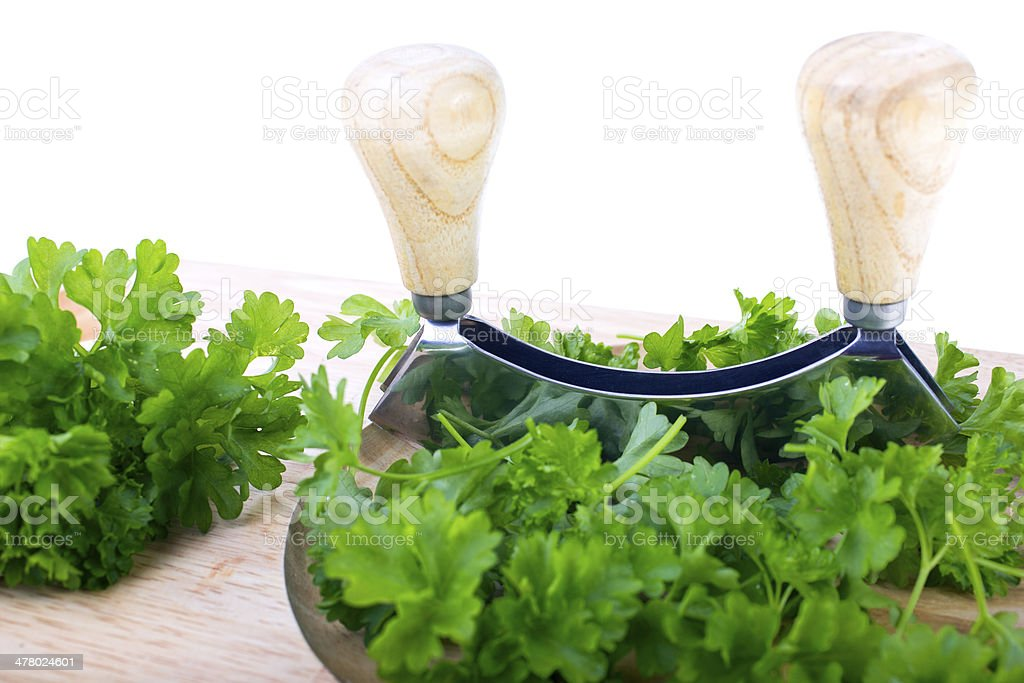 Chopping board with herb chopper and fresh parsley royalty-free stock photo