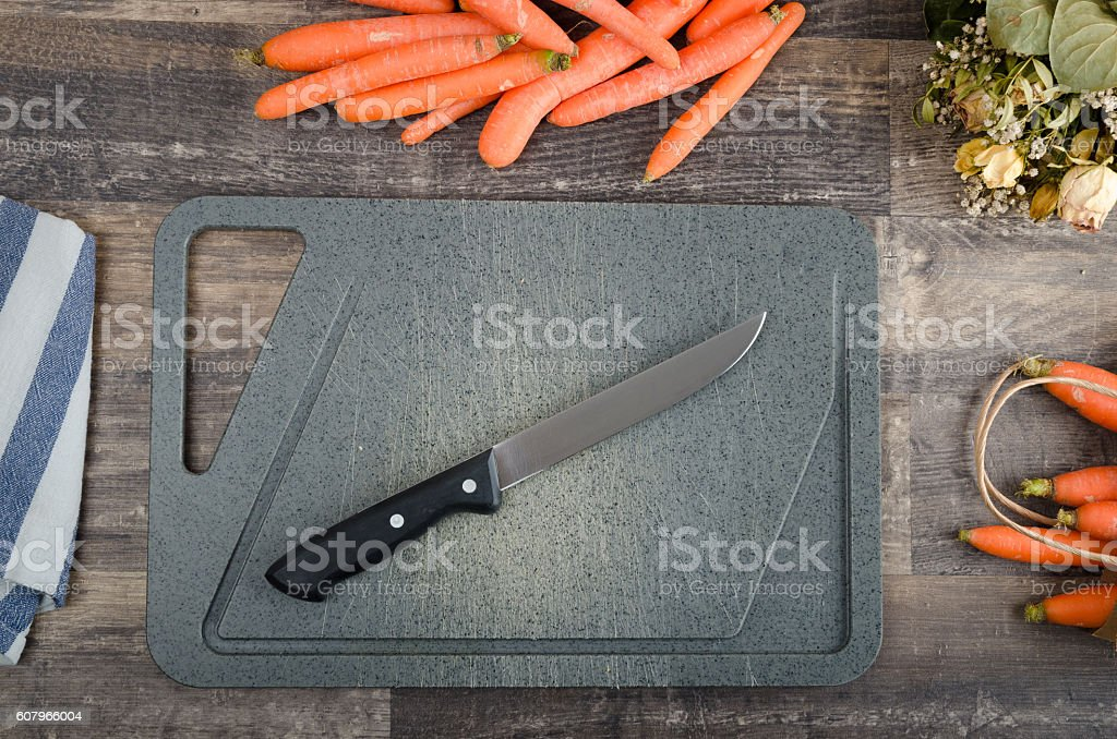 Chopping carrots on a rustic old vintage oak kitchen table stock photo