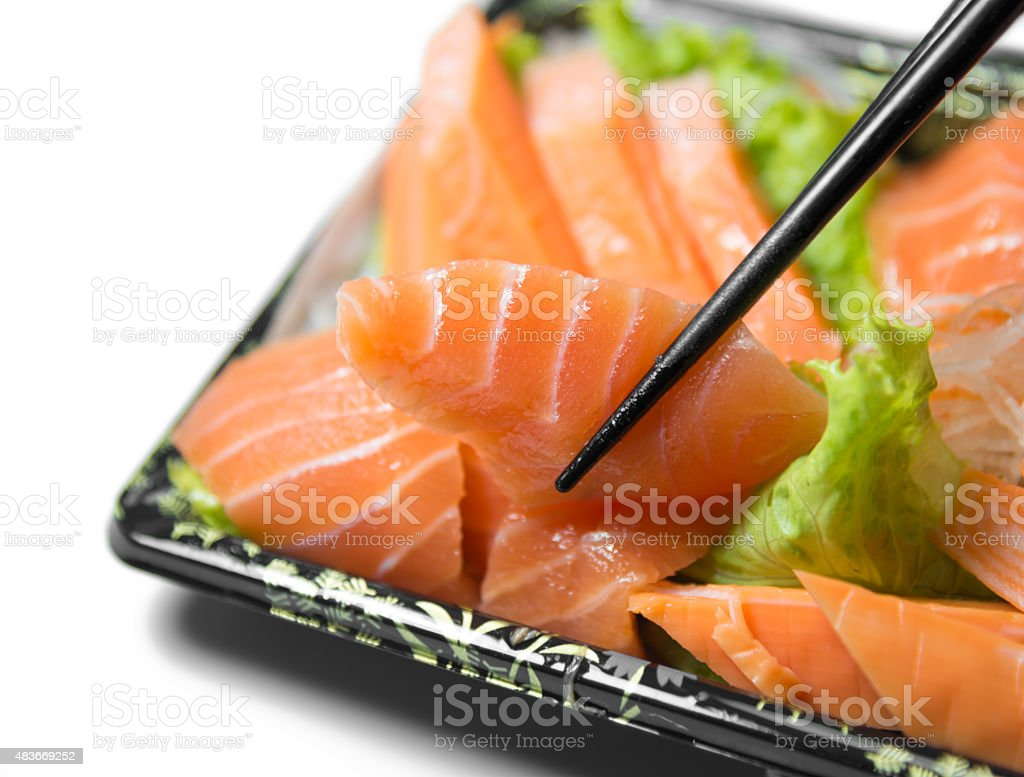 Chopstick grab a slice of Salmon Sashimi Japanese food   closeup stock photo