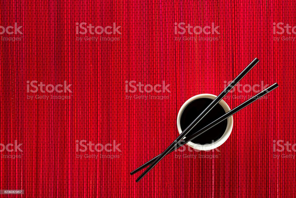 Chopsticks and bowl with soy sauce on bamboo mat stock photo