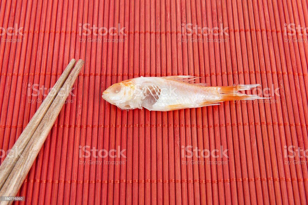 Chopsticks And Eaten Fish On Place Mat royalty-free stock photo
