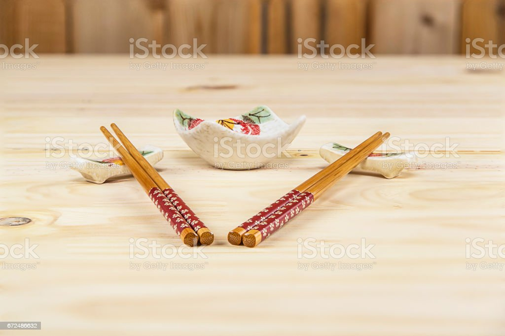 Chopsticks, Holder, and Sauce bowl on a Pine Table stock photo